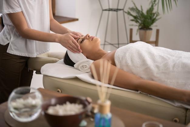Masaż tajski. atrakcyjna, zrelaksowana kobieta w salonie spa, ciesząc się masażem tajskim