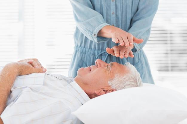 Masaż terapeuta wykonujący reiki nad człowiekiem