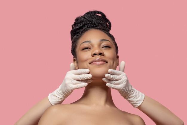 Masaż twarzy. afroamerykanka ma masaż twarzy i wygląda na zadowoloną