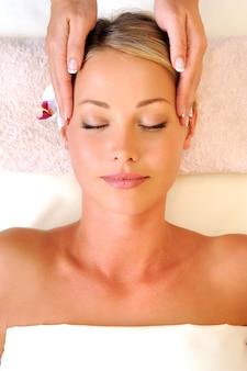 Masaż twarzy dla młodej kobiety w gabinecie kosmetycznym