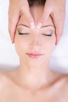 Masaż twarzy dla młodej kobiety w salonie spa
