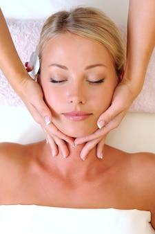Masaż twarzy dla pięknej młodej kobiety w gabinecie kosmetycznym