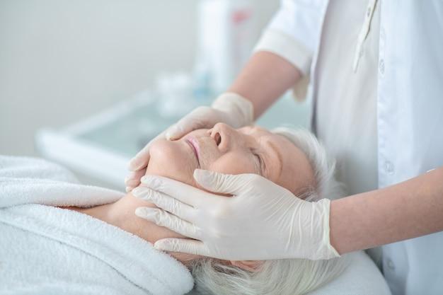 Masaż twarzy. dojrzała kobieta korzystająca z masażu twarzy i wyglądająca na zrelaksowaną