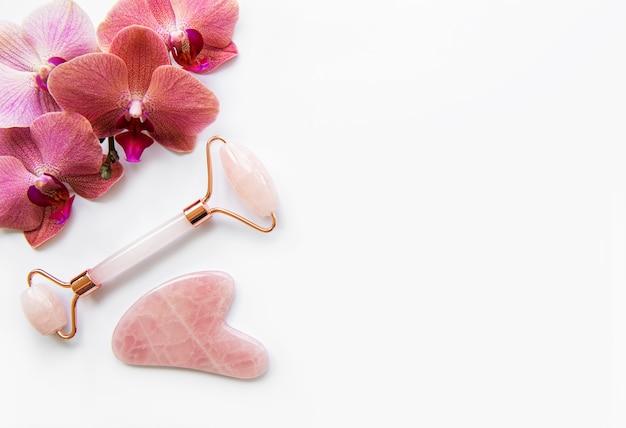 Masaż twarzy jadeitowymi rolkami i kwiatami orchidei na białej ścianie