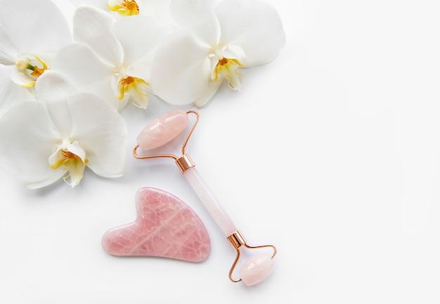 Masaż twarzy jadeitowymi rolkami i kwiatami orchidei na białym stole