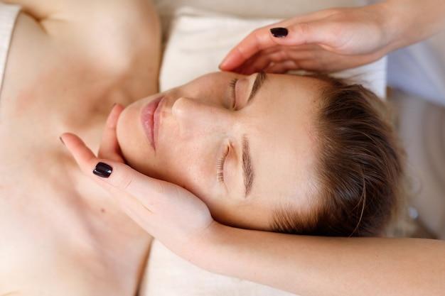 Masaż twarzy kobiety z bliska procedury przeciwstarzeniowe