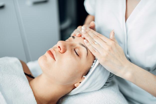 Masaż twarzy pacjentki, gabinet kosmetologii