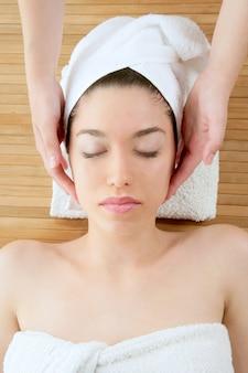 Masaż twarzy pięknej kobiety z białym ręcznikiem
