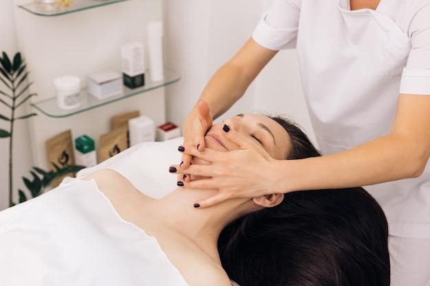 Masaż twarzy w salonie piękności spa kaukaska kobieta odbiera masaż twarzy w estetycznym salonie spa