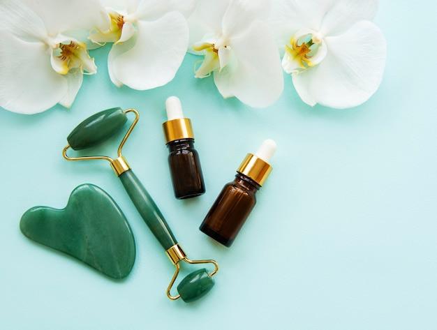 Masaż twarzy wałkiem jadeitowym i kosmetykiem na pastelowo-zielonej powierzchni