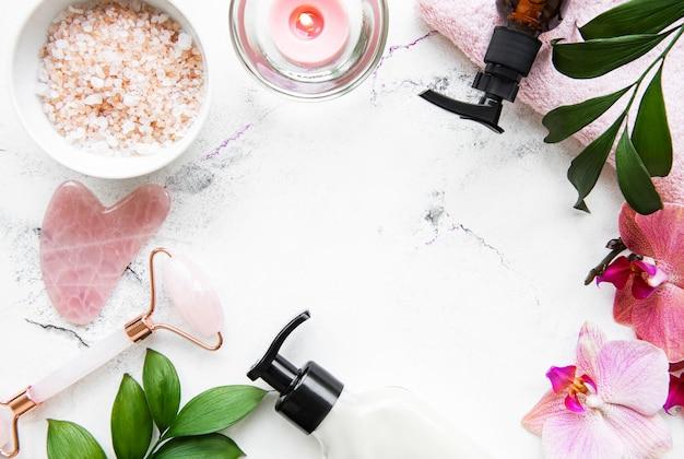 Masaż twarzy wałkiem jadeitowym i kosmetykiem na powierzchni białego marmuru