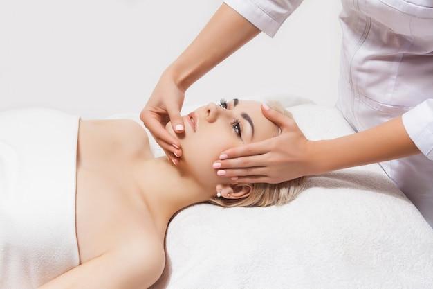 Masaż twarzy. zbliżenie: młoda kobieta odbiera masaż spa w salonie piękności i spa przez kosmetyczki. spa pielęgnacja skóry i ciała. pielęgnacja twarzy piękna. kosmetyka.