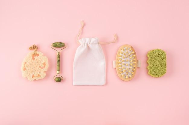 Masażer antycellulitowy, bambusowa gąbka, jadeitowy wałek do twarzy, bawełniana torba, gąbka loofah na pastelowym różu. zestaw akcesoriów łazienkowych. koncepcja zero waste.