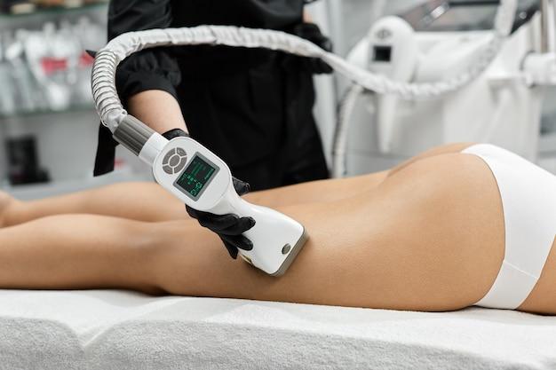 Masażer antycellulitowy na nogę kobiety w gabinecie kosmetycznym przez kosmetyczki w czarnych rękawiczkach