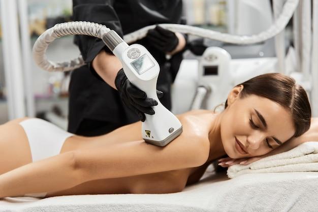 Masażer lpg na ładnej kobiecie z idealnym ciałem w centrum spa