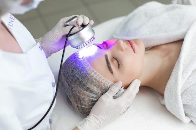 Masażer ultradźwiękowy. lekka kuracja skóry, kobieta w salonie piękności