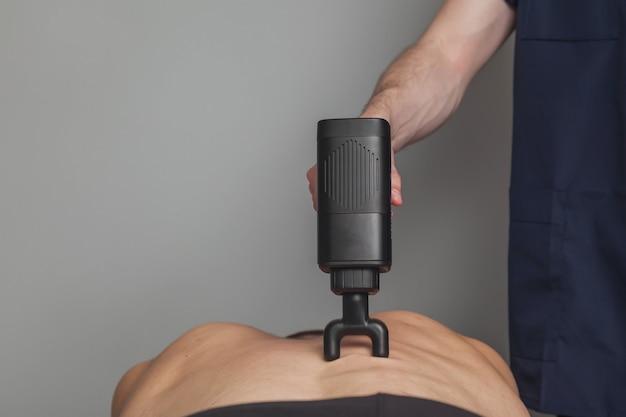 Masażysta leczy kontuzję profesjonalnego sportowca. masaże szokowe pistoletem sportowym w gabinecie lekarskim siłowni. terapia perkusyjna do masażu regeneracyjnego wysportowanego ciała. fizjoterapia