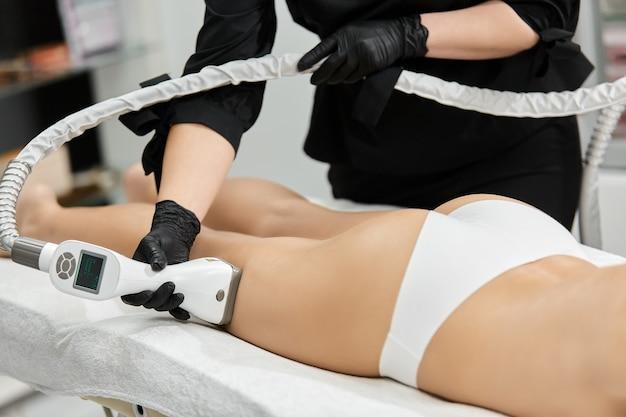 Masażysta leczy stronę nogi kobiety profesjonalnym urządzeniem na białym łóżku medycznym