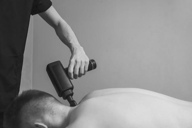 Masażysta leczy urazy profesjonalnego sportowca męskiego pacjenta