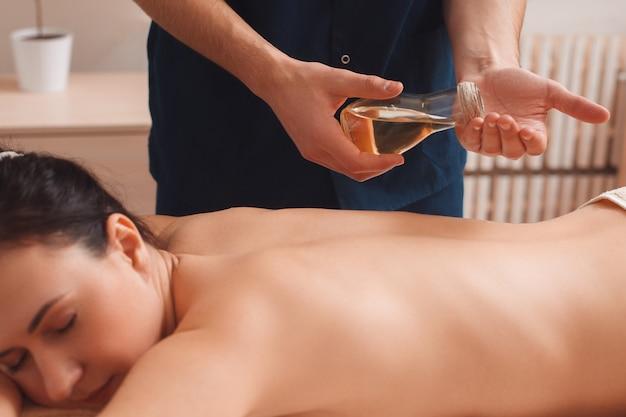 Masażysta masuje kobietę olejkiem aromatycznym
