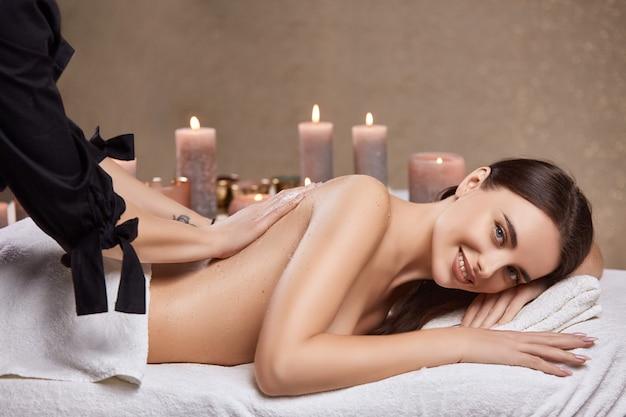 Masażysta masuje ładną dziewczynę na plecach kremem w salonie spa pełnym świec zapachowych