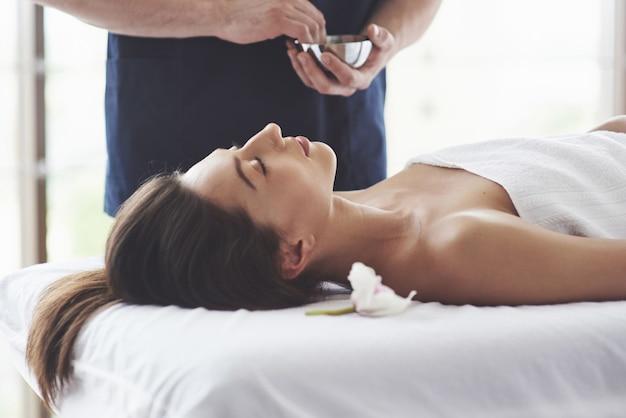Masażysta przygotowuje do zabiegu masaż o działaniu prozdrowotnym. przyjemność relaksu.