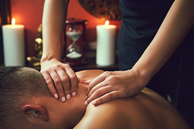 Masażysta robi masaż szyi na człowieka w salonie spa