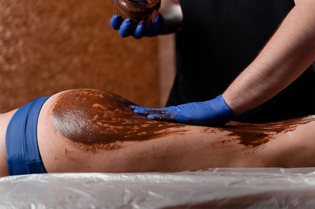 Masażysta smaruje czekoladą nogi i uda dziewczyny w centrum spa. zabieg upiększający okład czekoladowy.