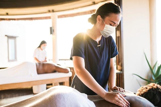 Masażysta spa z maską na twarz pracujący w nowej normie