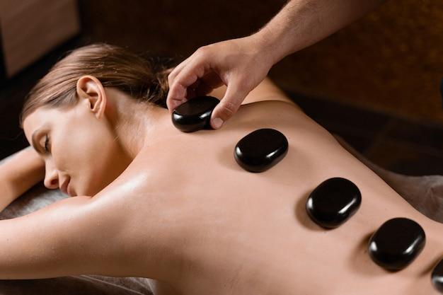 Masażysta umieścił gorący kamień na plecach kobiety. terapia manualna w spa.