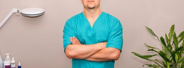 Masażysta w mundurze z rękami skrzyżowanymi stojący przy stole do masażu w klinice.