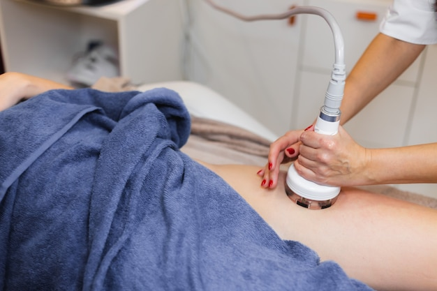 Masażysta wykonuje masaż antycellulitowy klientowi w gabinecie kosmetycznym przy użyciu olejku