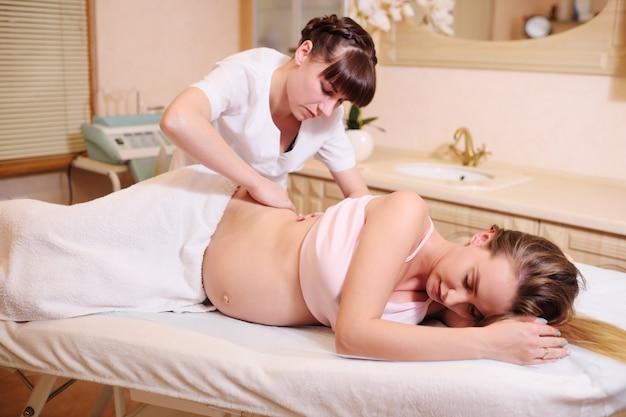 Masażysta wykonuje masaż brzucha dla kobiety w ciąży