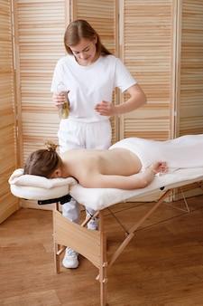 Masażysta wykonuje masaż olejkiem