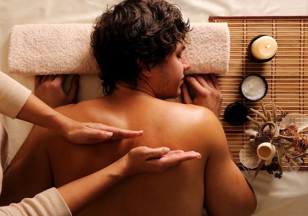 Masażysta wykonuje masaż pleców młodemu facetowi w salonie kosmetycznym