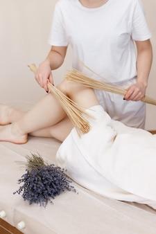 Masażysta wykonuje masaż stóp specjalnymi miotłami na kanapie. dbanie o siebie