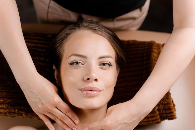 Masażysta wykonuje masaż twarzy w spa dla modelki o doskonałej skórze. zabieg kosmetyczny.