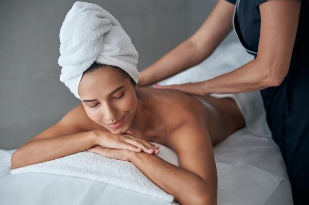 Masażystka masuje kobiece plecy w salonie spa