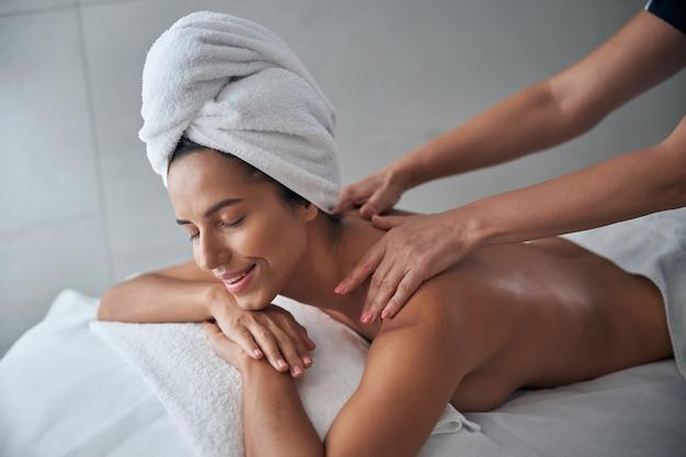 Masażystka ręce masujące młodą kobietę z powrotem w salonie spa