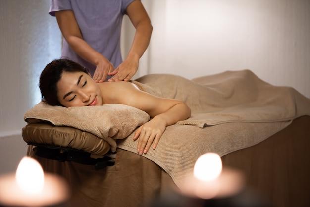 Masażystka robi masaż na azjatyckie ciało kobiety w salonie spa.