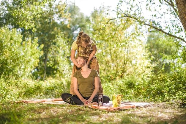 Masażystka wykonująca masaż na trawie