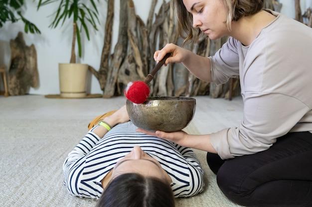Masażystka wykonuje tradycyjną tybetańską terapię dźwiękową masaż misami śpiewającymi u zrelaksowanej kobiety