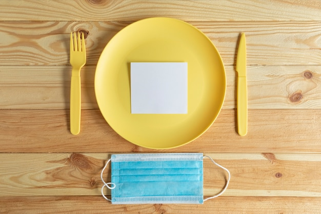 Maseczka do twarzy na drewnianym stole i pusty papier na talerzu