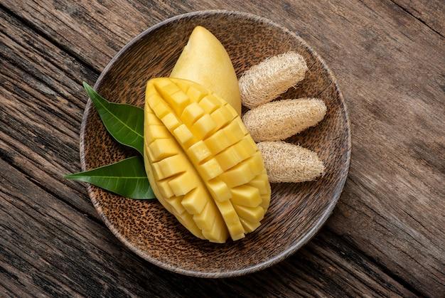 Maseczka do twarzy z dojrzałymi owocami mango do pielęgnacji skóry i na stare drewno. widok z góry, układana na płasko.