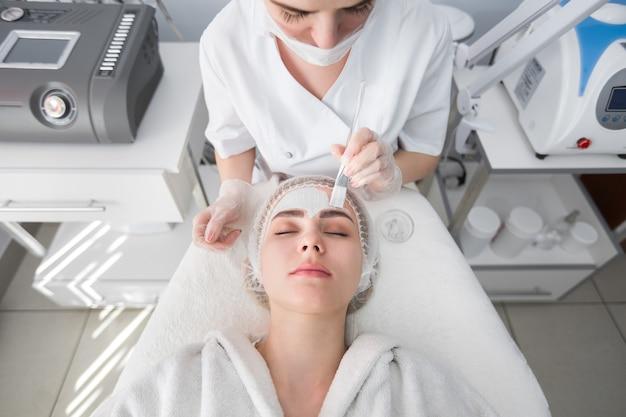 Maseczka peelingująca do twarzy, zabiegi upiększające w spa, pielęgnacja skóry. kobieta coraz pielęgnacja twarzy przez kosmetyczkę w salonie spa