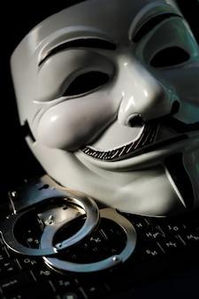 Maska ananimus z kajdankami na klawiaturze laptopa. przestępczość hakerska. koncepcja cyberprzestępczości. zdjęcie wysokiej jakości