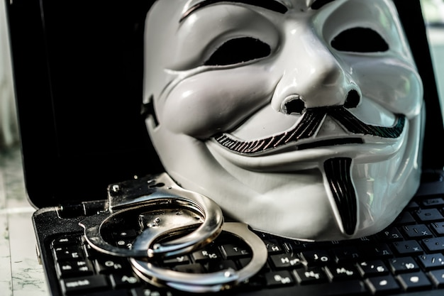 Maska ananimus z kajdankami na klawiaturze laptopa. przestępczość hakerska. zdjęcie wysokiej jakości