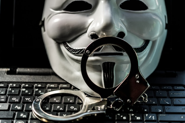 Maska ananimus z kajdankami na klawiaturze laptopa. zdjęcie wysokiej jakości