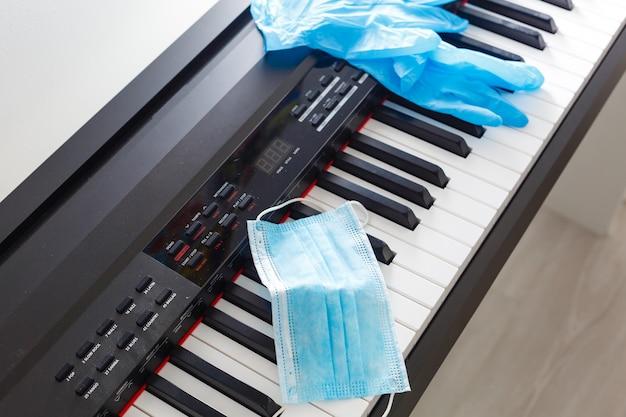 Maska antywirusowa i rękawiczki leżą na pianinie