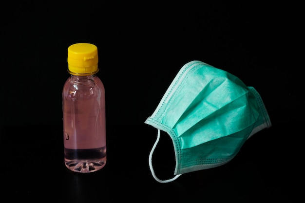 Maska chirurgiczna (doctor) z żelem do mycia rąk na białym tle na czarnym tle - w celu zapobiegania kurzu (pm 2.5), chorobom (koronawirus lub covid-19).